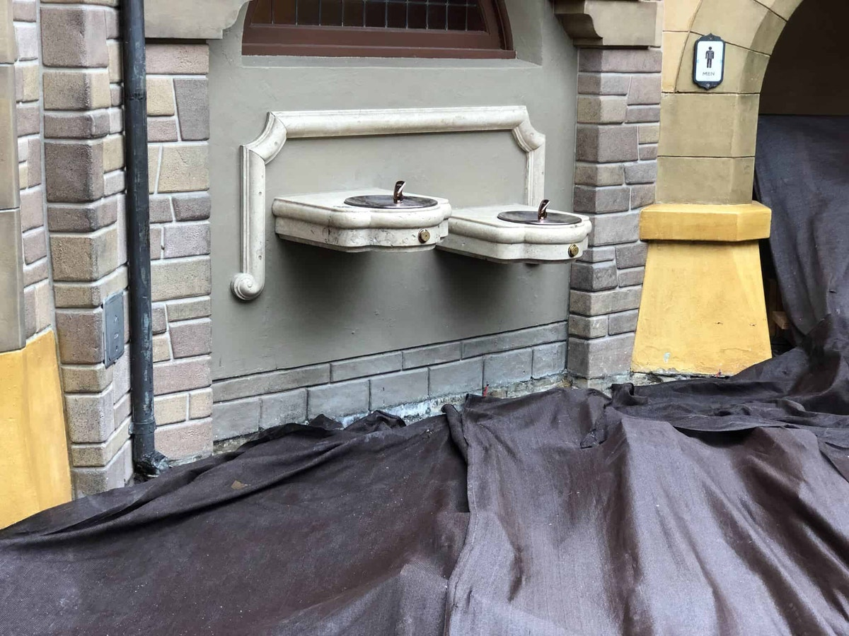 Construction on the ground around the water fountains outside Fantasyland restrooms